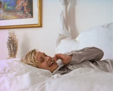 Blonde caucasian woman in silver pygamas lays on white bed talking on the phone Stock Footage