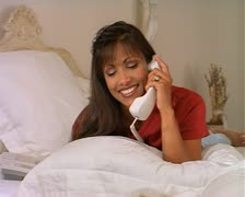 Ethnic woman lays on white bed talking and laughing on the phone Stock Footage