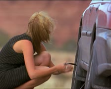 Blonde caucasian woman in black dress changes tire on her car Stock Footage