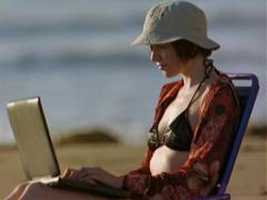 Caucasian woman in black bikini, red shirt, and white hat sits on the beach in Stock Footage