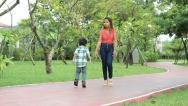 Cute Asian Boy Doing A Crazy Walk In Park Stock Footage