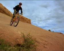 Slow motion wide shot of a female mountain biker as she rides down a hill and Stock Footage