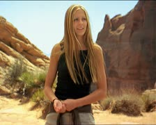 Medium shot of a young attractive caucasian female in a red rock canyon as she Stock Footage