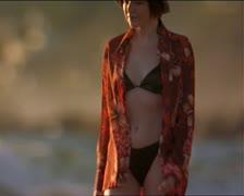 Medium shot of a caucasian woman in a black bikini as she walks along the beach Stock Footage