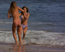 Wide shot as two attractive women in bikinis run play and frolic in the crashing Stock Footage