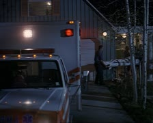 Wide shot as paramedics wheel a gurney out of a house and into a parked Stock Footage