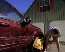 Medium tracking shot as a father and his little boy wash the tire and the rest Stock Footage