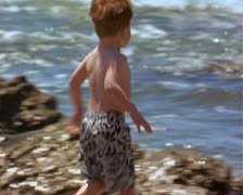 Medium shot of a little red headed boy as he runs to the waters edge to play Stock Footage