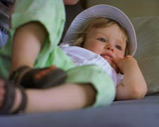 Medium close up of a little girl laying down as she is playfully attacked by her Stock Footage