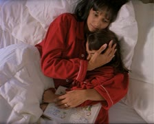 medium shot of an ethnic mother and daughter in their red pajamas as they cuddle - stock footage