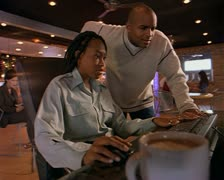 Wide shot of a young african american couple in a cafe as they lokk at and work Stock Footage