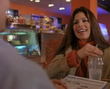Medium over the shoulder shot of an attractive female as she sits in a cafe on a Stock Footage
