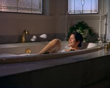 Medium tracking shot of a woman relaxing in the bathtub as she plays with the Stock Footage