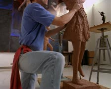 Medium shot and move up of a caucasian artist as he carves and molds the clay to Stock Footage