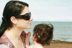 Mother and daughter enjoy hot summer weather at the beach. Stock Photos
