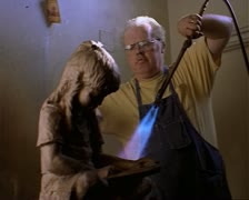 Medium shot of an older caucasian man as he bronzes a statue of a little girl by Stock Footage