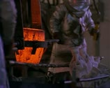 Stock Video Footage of medium shot as two workmen in heat resistant suits lift and pour molten metal