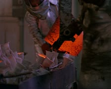 Medium shot as two workmen in heat resistant suits lift and pour molten metal Stock Footage