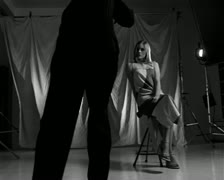 Black and white wide tracking shot of a female modeling in a studio for a male Stock Footage