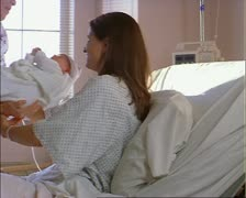 Tracking shot of a young caucasian mother as a nurse hands her her newborn baby Stock Footage