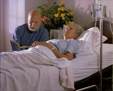 Tracking shot of an elderly caucasian man as he reads a book to his ill wife as Stock Footage