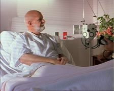 Tracking shot of an elderly caucasian male patient as a male nurse arrives to Stock Footage