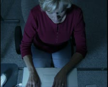 High angle medium shot of a blonde woman working at her computer late into the Stock Footage