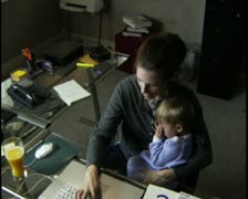High angle medium shot of a woman in her home office with a child on her lap Stock Footage
