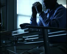 Medium shot of a man looking worried and then making a phone call late in the Stock Footage