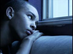 close up shot of a teenage male at night as he looks sadly out the window - stock footage