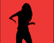 medium shot of a young woman as she dances playfully silhouetted against red - stock footage