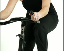 Close-up of an adult woman riding an exercise bike - stock footage
