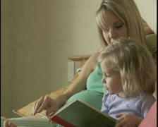 Pregnant woman reading story to young girl Stock Footage