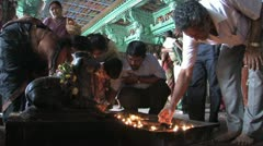 Hindu worshippers light candles Stock Footage