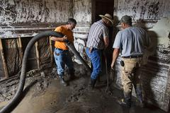 Men pumping water mud from flooded home 1948.jpg - stock photo