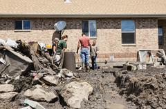 Friends helping clean mud water home property flood 2031.jpg - stock photo
