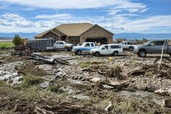 Home damaged by flash flood neighbors helping to clean 1844.jpg - stock photo