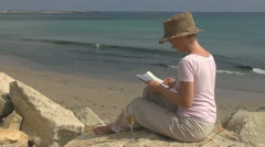 Beautiful woman reading and drinking white wine on the beach, lifestyle, ocean Stock Footage
