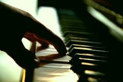 Hand on piano in dark room Stock Photos