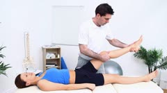 The leg of a woman being stretched by a physiotherapist Stock Footage