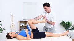 Physiotherapist stretching the leg of his woman patient Stock Footage