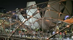 People crossing the helix bridge to Marina Bay Sands hotel in Singapore Stock Footage