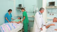 Medical team talking with a patient in a bed ward Stock Footage