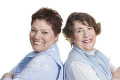 Two smiling women shoulder to shoulder Stock Photos