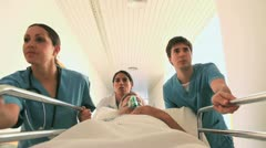 Nurses driving a patient on his bed with an oxygen mask - stock footage