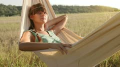 Pretty young girl swinging on hammock at sunset - stock footage