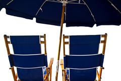 Beach chairs and umbrella isolated on white - stock photo