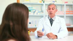 Pharmacist talking to a customer while holding a box of pills - stock footage