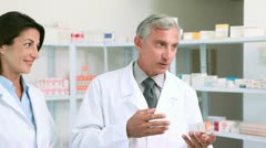 Pharmacist holding a box of pills while talking to a customer - stock footage