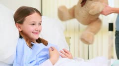 Happy woman giving a teddy bear to a girl in a bed Stock Footage